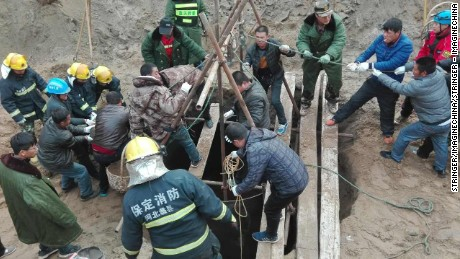 Rescuers and volunteers search for a 5-year-old boy after he fell down and was trapped in a 40 meter deep abandoned well.