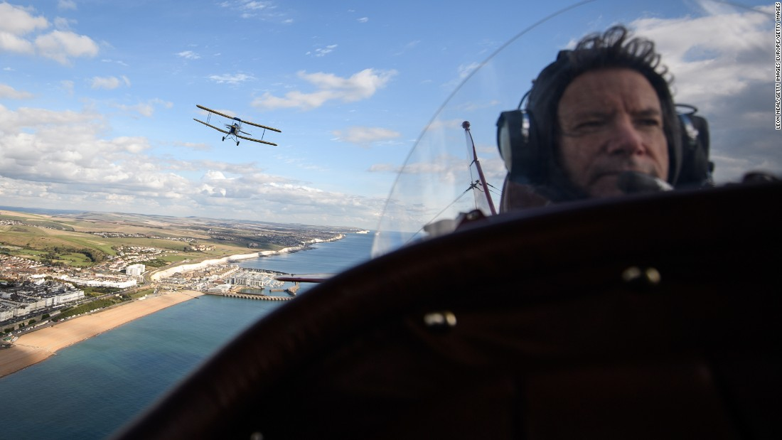 Tiger Moth DH82A, flown over the English coast by pilot Ian Perry, is seen over the shoulder of pilot Pedro Langdon during a promotional event ahead of the rally.