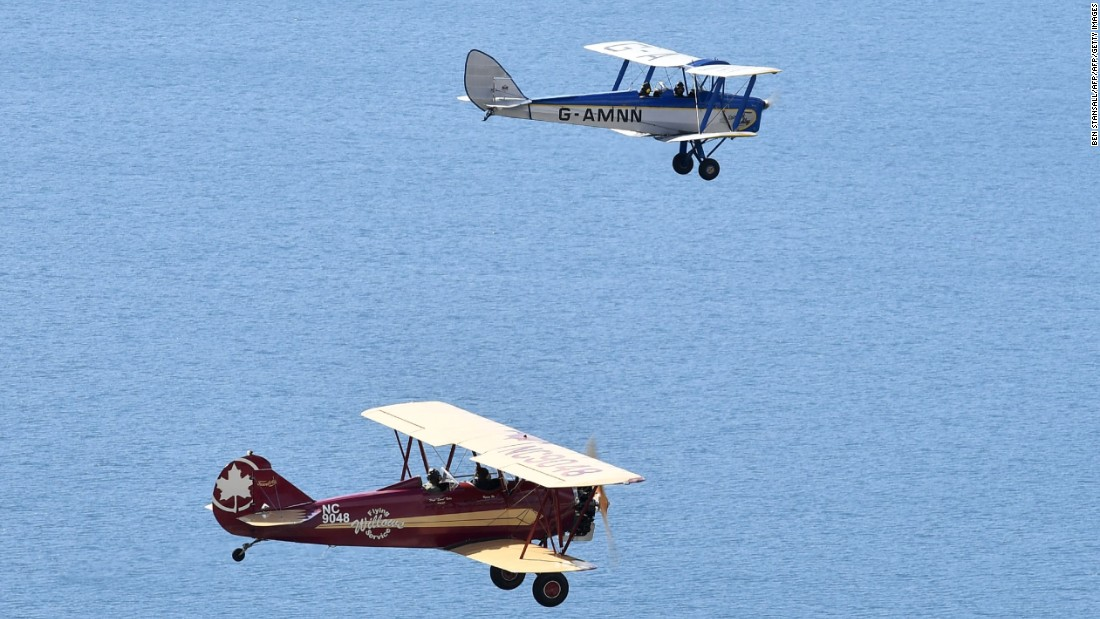 Tiger Moth and Travel Air 4000 biplane practice off the coast of the UK. Several of the participating pilots are making a biplane voyage for the first time.
