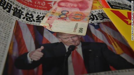 "A Chinese newspaper featuring a photo of US President-elect Donald Trump that reads ""President Trump shakes America"", is partially covered by a 100 Yuan note on a news stand, as a customer (not pictured) waits to buy a phone card in Beijing on November 10, 2016. The American public on November 9 voted for the Republican candidate Donald Trump to be the 45th President of the United States.  / AFP / GREG BAKER        (Photo credit should read GREG BAKER/AFP/Getty Images)"