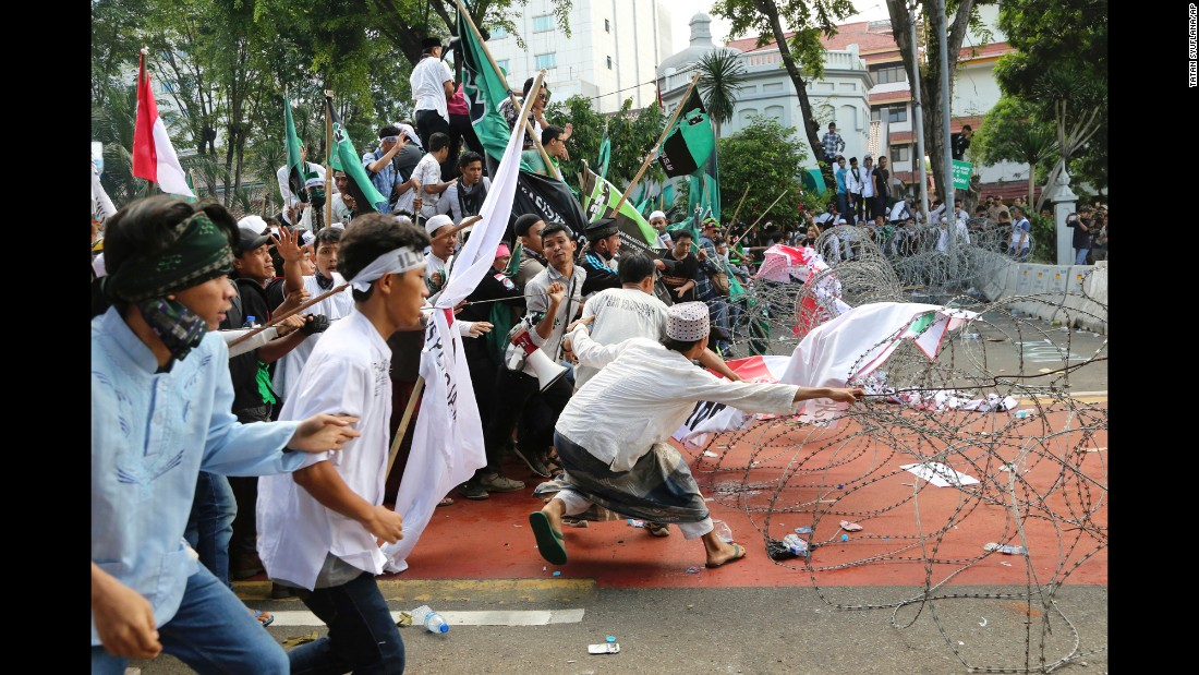 "Muslim protesters pull barbed wire blocking a road that leads to the presidential palace during a rally against Gov. Basuki Tjahaja Purnama in Jakarta, Indonesia, on Friday, November 4. Purnama, commonly known as Ahok, is a member of Indonesia's Christian minority and is <a href=""http://www.cnn.com/2016/11/03/asia/jakarta-islamist-governor-protest/"" target=""_blank"">alleged to have insulted Islam</a> by criticizing his opponent's use of a Quranic verse in a speech."