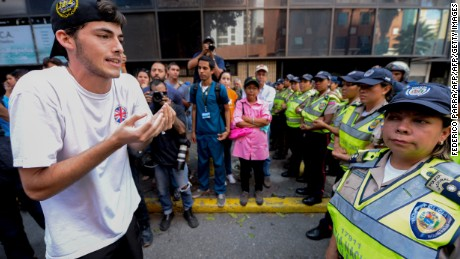 An university student faces a line of police officers blocking the way of a march protesting against the government of President Nicolas Maduro in Caracas on November 10, 2016. / AFP / FEDERICO PARRA        (Photo credit should read FEDERICO PARRA/AFP/Getty Images)