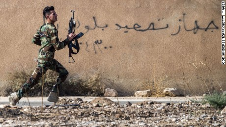 """TOPSHOT - A Peshmerga fighter runs to take position as the Iraqi Kurdish forces pushed deeper into the town of Bashiqa during street battles against Islamic State (IS) group jihadists on November 8, 2016.  Capturing Bashiqa would be one of the final steps in securing the eastern approaches to Mosul, three weeks into an offensive by Iraqi forces to retake the country's second city. The town was under the """"complete control"""" of Kurdish peshmerga forces, Jabbar Yawar, the secretary general of the Kurdish regional ministry responsible for the fighters, told AFP. / AFP / Odd ANDERSEN        (Photo credit should read ODD ANDERSEN/AFP/Getty Images)"""