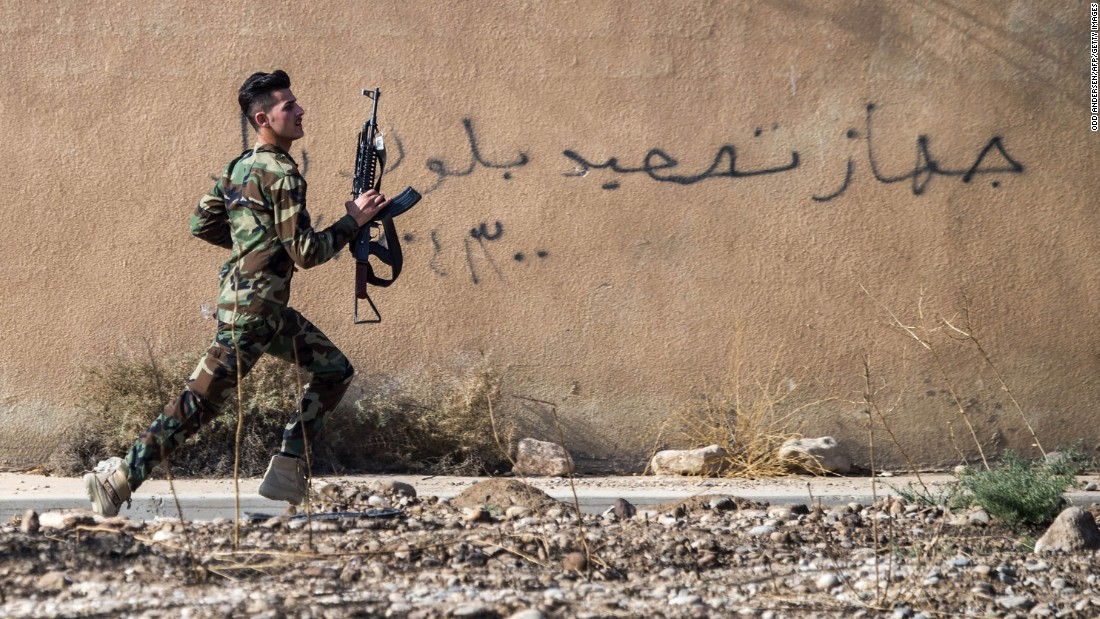 A Kurdish Peshmerga fighter races to take a position on a street in Bashiqa as coalition forces battled to reclaim the town from ISIS control on November 8.