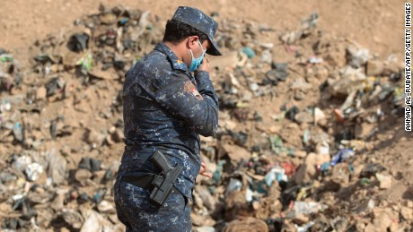 An Iraqi soldier checks a mass grave in Hamam al-Alil, an area recently retaken from ISIS.