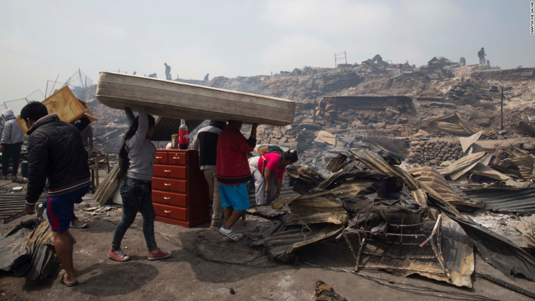 A family salvages a mattress from charred debris after an early morning fire that destroyed hundreds of homes in the indigenous Amazonian community of Cantagallo, in Lima, Peru, on Friday, November 4.
