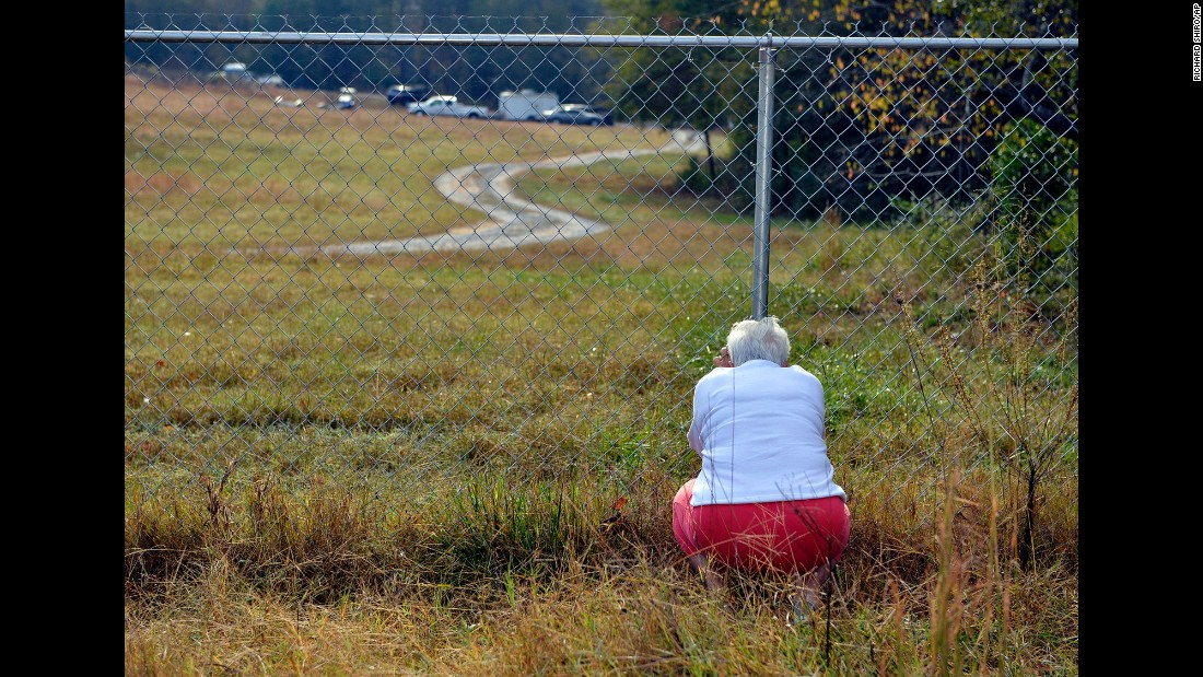 "Frances Bradley prays at the fence separating her home from Todd  Kohlhepp's home in Woodruff, South Carolina, on Sunday, November 6. Kohlhepp, a 45-year-old real estate agent who <a href=""http://www.cnn.com/2016/11/05/us/south-carolina-chained-womans-boyfriend-body-idd/"" target=""_blank"">confessed to a 2003 quadruple homicide</a>, has now been <a href=""http://www.cnn.com/2016/11/03/us/missing-south-carolina-woman-found/index.html"" target=""_blank"">accused of kidnapping a woman and holding her captive for two months</a>."