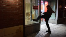 A protester kicks the window of a Bank of America branch in Portland, Oregon, on November 10. What started out as a peaceful march with more than 4,000 people <a href=