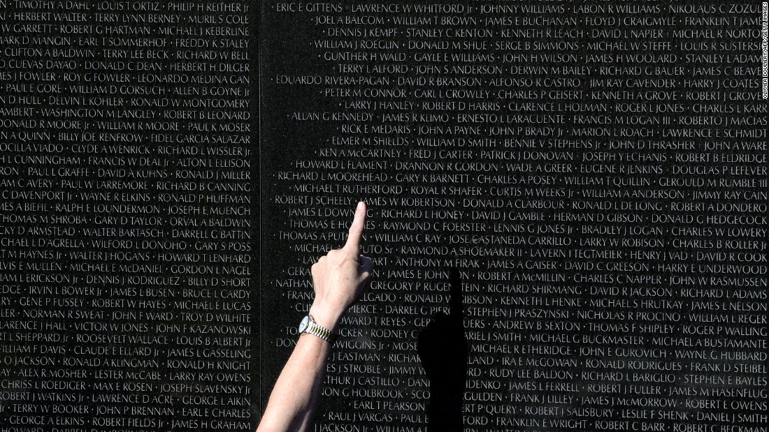 A Park Service volunteer in Washington points to a name on the Vietnam Veterans Memorial on November 11.