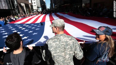 People hold a large U.S. flag while marching up Fifth Avenue during the Veterans Day parade, Friday, Nov. 11, 2016, in New York. (AP Photo/Julio Cortez)