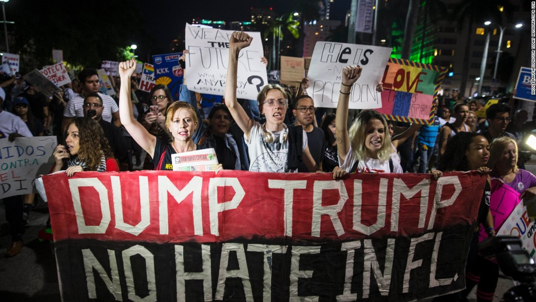People protest Trump during a march in downtown Miami on Friday, November 11.