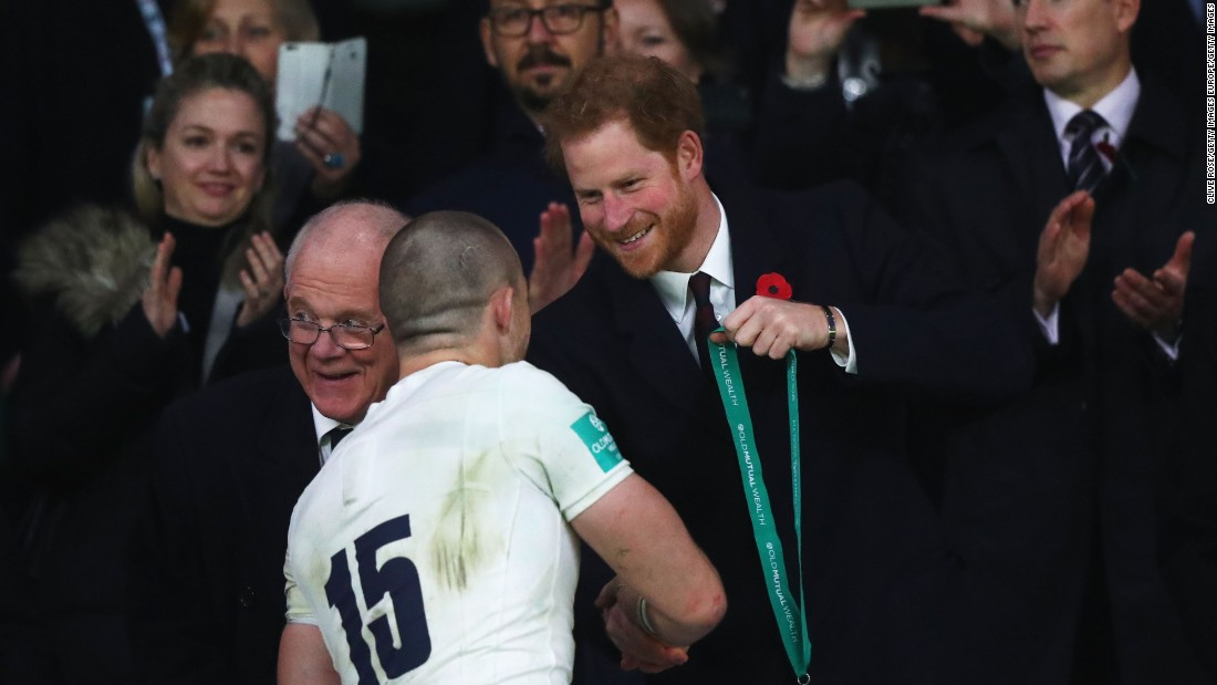 Prince Harry presents a winner's medal to Mike Brown of England.