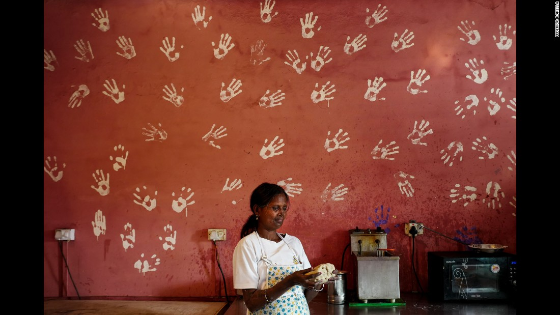 Gita bakes bread in the cafe's kitchen. On the wall are the imprints of all the survivors' hands.