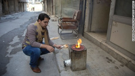 Khaled Kurdiyah, a Syrian man who runs an internet cafe, uses a metal container outfitted with a fan that creates a highly-controlled bonfire to replace rare gas-fired stoves while using minimal firewood, in Aleppo's besieged eastern Karam al-Jabal district, on October 31, 2016.Cigarettes stuffed with grape leaves instead of tobacco, gardens on bombed-out rooftops, and batteries powered by rusted bicycles: In Syria's besieged eastern Aleppo, necessity is the mother of invention. More than 250,000 people have been under a government siege in the rebel-held side of the northern city since July, without access to aid, food, fuel, medicine or even cigarettes, sparking severe shortages and exorbitant prices for the few basic goods available, and has forced residents to find innovative ways to cope. / AFP / KARAM AL-MASRI        (Photo credit should read KARAM AL-MASRI/AFP/Getty Images)