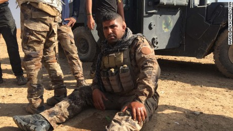 An Iraqi soldier sits on the ground in shock after his unit retreated from a battle with ISIS in eastern Mosul -- he said an ISIS suicide car bomb detonated near his Humvee.