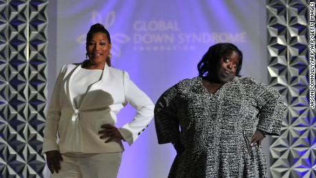 "Queen Latifah walks the runway with DeOndra Dixon during the 2016 Global Down Syndrome Foundation ""Be Beautiful, Be Yourself"" fashion show."