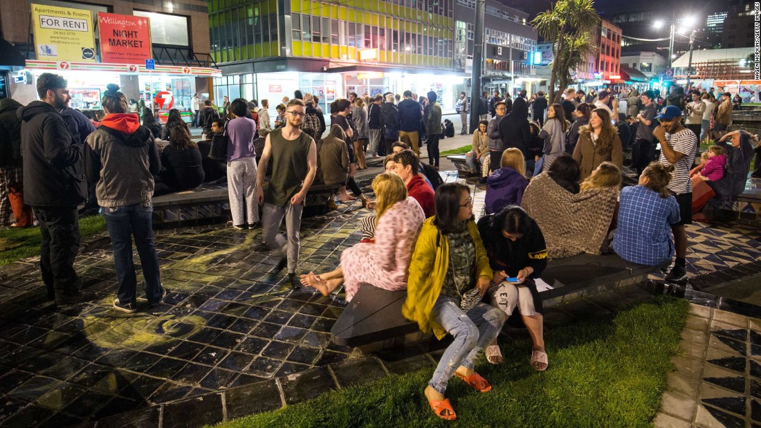 People wait in Te Aro Park after being evacuated from nearby buildings.