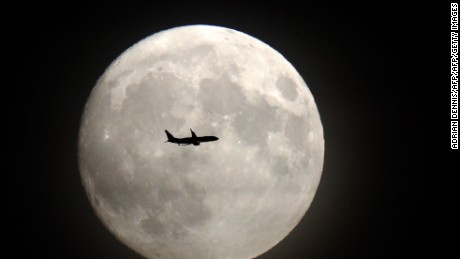 A commerical jet flies in front of the moon on its approach to Heathrow airport on November 13, 2016.