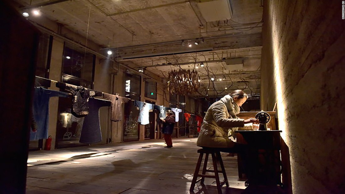 Ma Ke uses a vintage sewing machine next to the clothes exhibited in the Wuyong Space in Beijing.