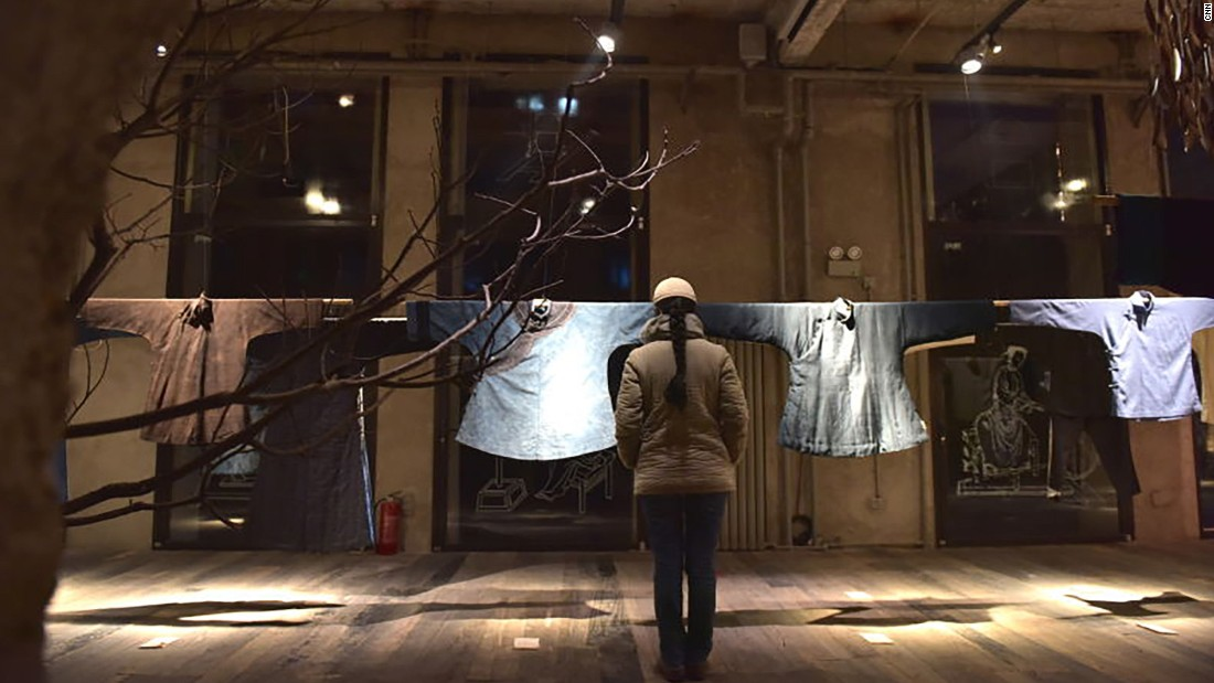 Ma Ke adjusts her exhibits -- clothes she collected to convey family stories -- in Wuyong Space in Beijing.