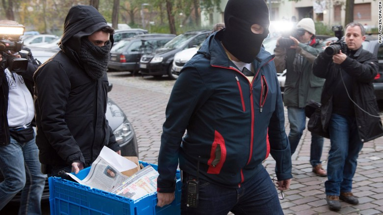 Police officers transport materials seized in the raid on True Religion (Photo Courtesy of CNN)