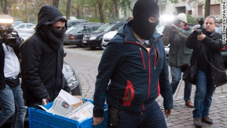 epa05631938 Police officers carry a case containing seized evidence during a raid in Berlin, Germany, 15 November 2016. Several police officers took part in an anti-terrorism raid against suspected supporters of the Islamic State (IS or ISIS) militant group. Authorities held raids against Islamist networks in ten German states.  EPA/PAUL ZINKEN