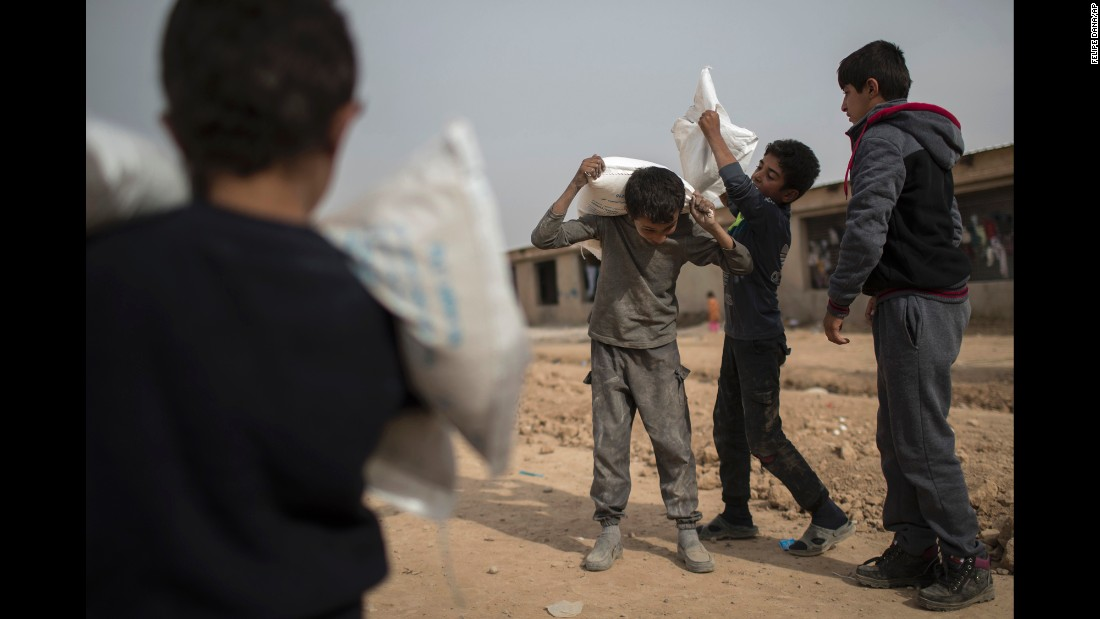 Iraqi boys who were displaced by fighting in Mosul carry food supplies at a camp in Hassan Sham, Iraq, on Thursday, November 10.