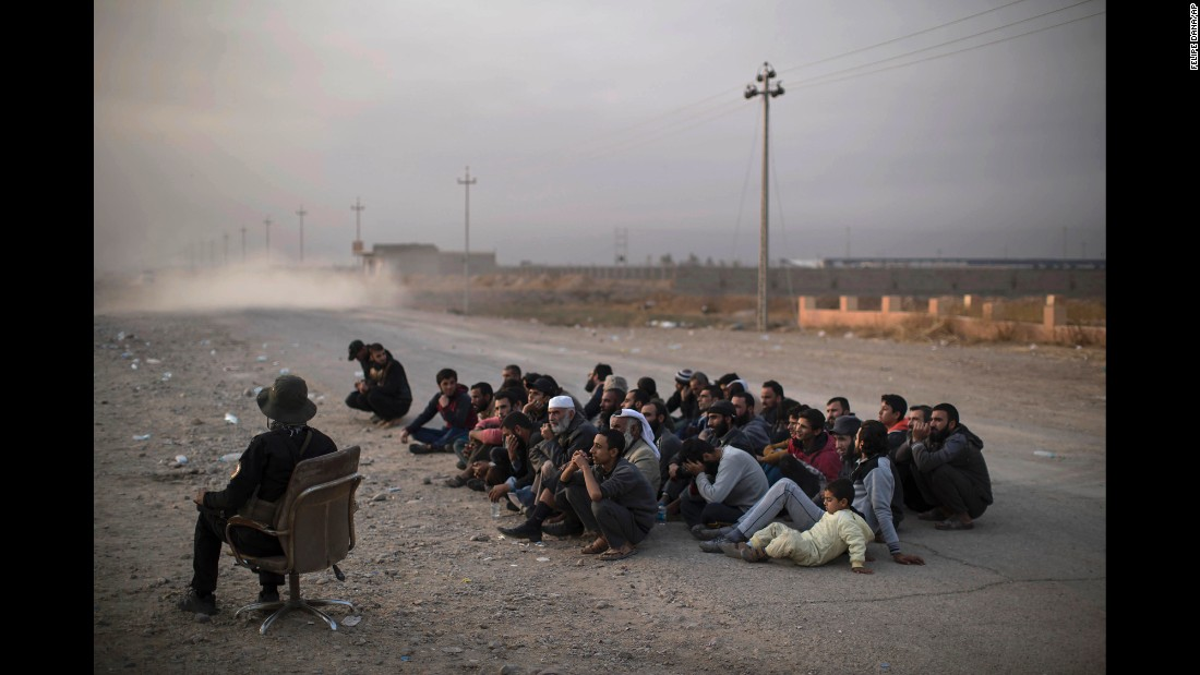 Civilians fleeing the war zone wait for their documents to be reviewed at a checkpoint near Bartella on Monday, November 14.