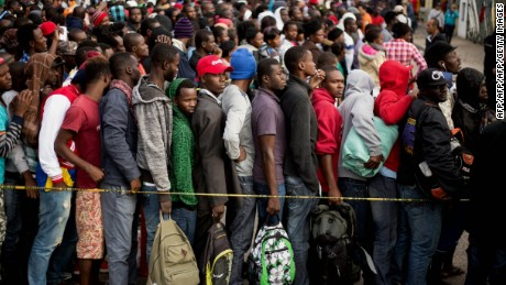 Haitian and African migrants seeking for asylum in the United States, line up outside a Mexican Migration office, on October 3, 2016, in Tijuana, northwestern Mexico. / AFP / GUILLERMO ARIAS        (Photo credit should read GUILLERMO ARIAS/AFP/Getty Images)
