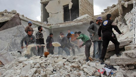 Rescuers and civilians inspect a destroyed building in the Syrian village of Kfar Jales, on the outskirts of Idlib, following air strikes by Syrian and Russian warplanes on November 16, 2016.