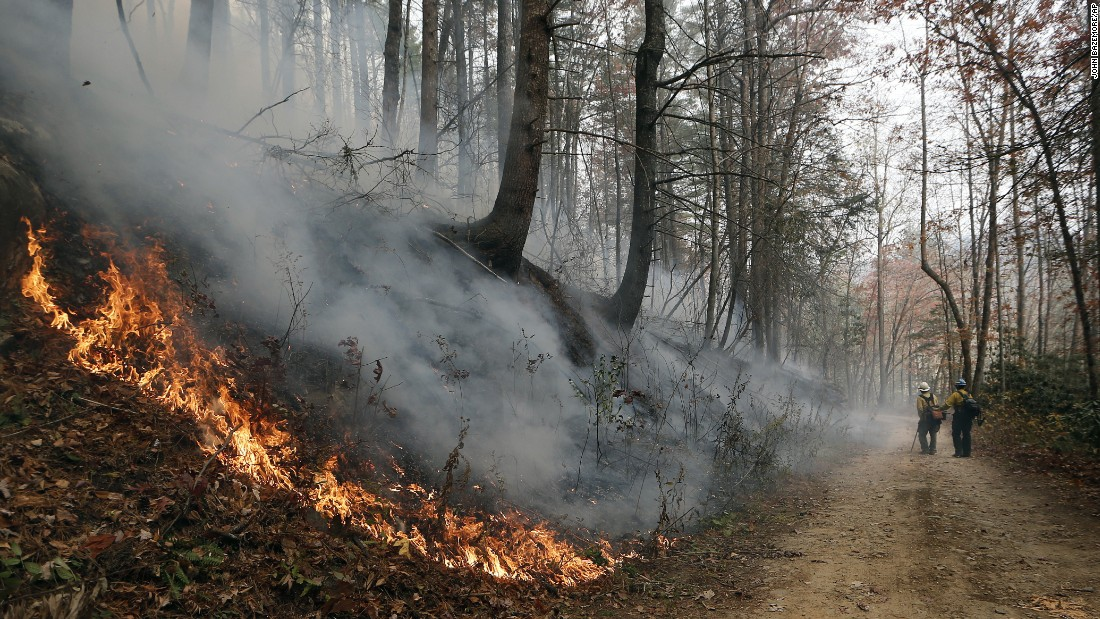 Firefighters walk down a dirt road as a wildfire burns a hillside in Clayton, Georgia, on Tuesday, November 15.