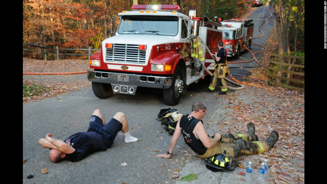 Exhausted firefighters take a break in Waldens Creek, Tennessee, on Monday, November 14.