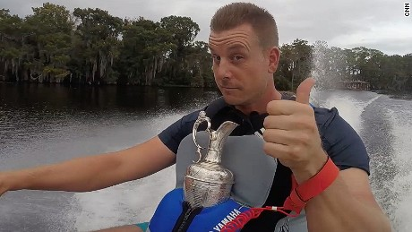 Open champion Henrik Stenson jet skiing in Florida with golf's famous Claret Jug.