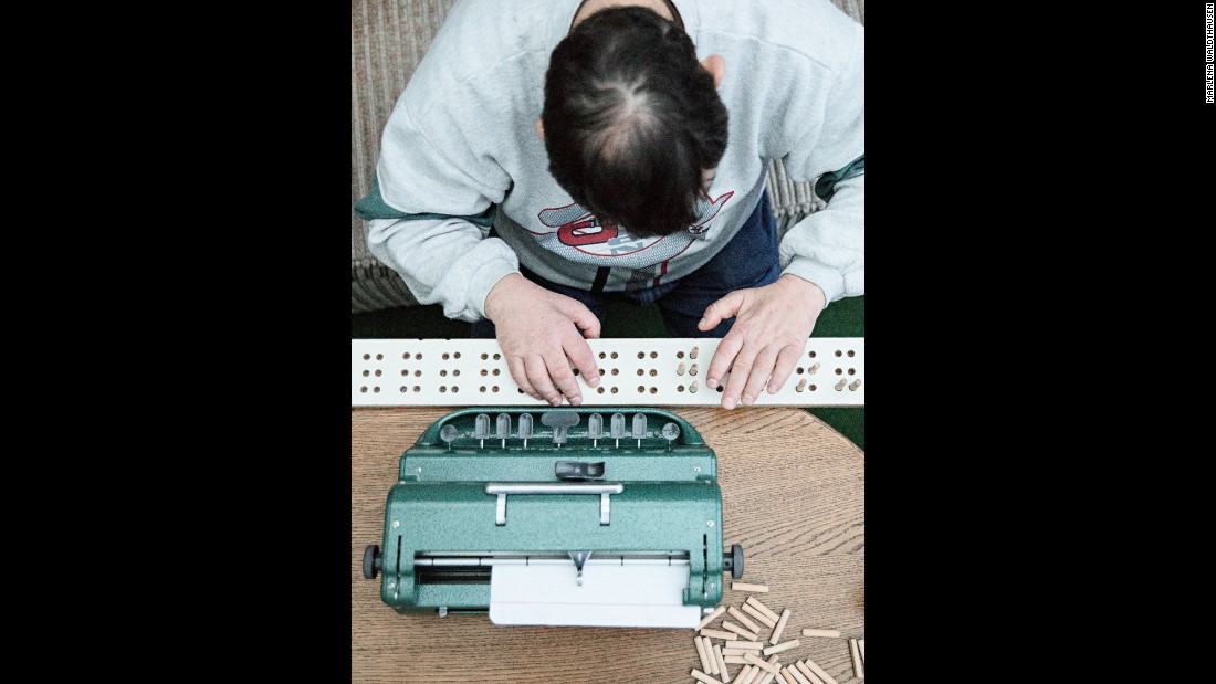 Jörg practices typing on a braille typewriter. His parents made him a wooden board with small wooden pins so he can feel the letters.