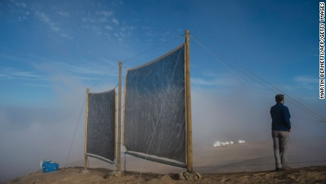 The head of research of the Institute of Geography of the Catholic University of Chile, Camilo del Rio, walks near a fog collection system at the Atacama desert in Iquique, some 2000 km north of Santiago, on April 19, 2016.  The collection of water from fog is done using large pieces of vertical canvas to make the fog condense into droplets of water and flow down into a trough.  / AFP / MARTIN BERNETTI        (Photo credit should read MARTIN BERNETTI/AFP/Getty Images)