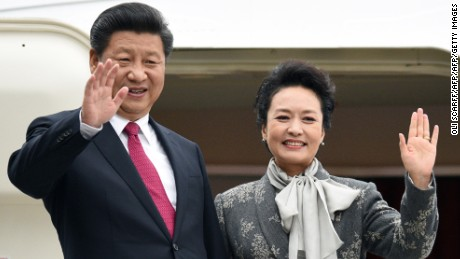 Chinese President Xi Jinping (L) and his wife Peng Liyuan wave as they board an Air China plane at Manchester airport in Manchester, northern England at the end of their state visit to Britain on October 23, 2015.   AFP PHOTO / OLI SCARFF        (Photo credit should read OLI SCARFF/AFP/Getty Images)