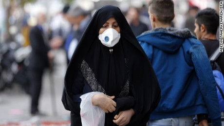An Iranian woman wears mask as she walk in a street in Tehran on November 16, 2016.
