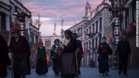 TOPSHOT - This picture taken on September 11, 2016 shows pilgrims walking and praying near the Jokhang Temple in the regional capital Lhasa, in China's Tibet Autonomous Region. / AFP / JOHANNES EISELE        (Photo credit should read JOHANNES EISELE/AFP/Getty Images)