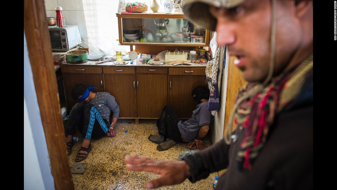 "A member of Iraq's special forces guards two suspected ISIS fighters found hiding in a house in Mosul, Iraq, on Friday, November 11. <a href=""http://www.cnn.com/2016/10/17/world/gallery/mosul/index.html"" target=""_blank"">An Iraqi-led offensive</a> was launched in October to reclaim Mosul, Iraq's second-largest city and the last major stronghold for ISIS in the country."