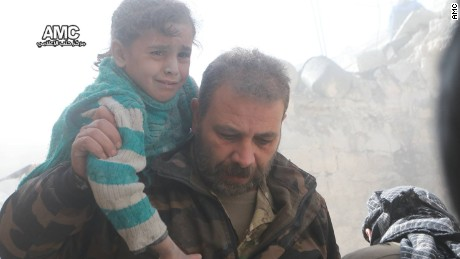 A man carries a child to safety in the wake of the airstrikes in Aleppo.