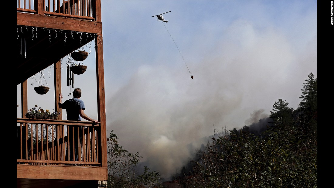 "Eric Willey looks on from the porch of his home as a helicopter fights a wildfire in Tate City, Georgia, on Wednesday, November 16. More than 30 large wildfires <a href=""http://www.cnn.com/2016/11/16/us/gallery/southern-wildfires/index.html"" target=""_blank"">have left a trail of destruction</a> through 80,000 acres of North Carolina, South Carolina, Georgia, Tennessee, Alabama and Kentucky, according to the US Forest Service."