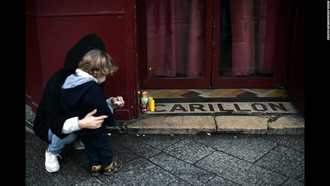 "A woman and her child lay candles outside of a Paris restaurant on Sunday, November 13 -- <a href=""http://www.cnn.com/2016/11/13/europe/paris-attacks-one-year-on/"" target=""_blank"">one year after</a> terrorist attacks killed 130 people in the French capital."