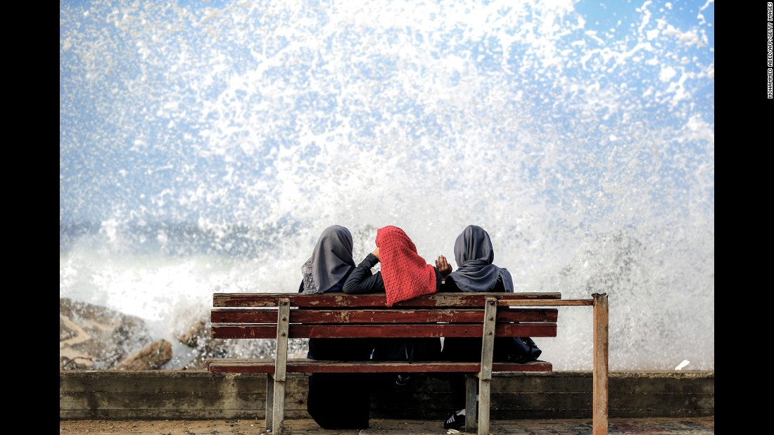 Three women watch waves hit a beachfront in Gaza City on Thursday, November 17.