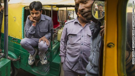 Sarvesh on his auto rickshaw with other drivers.