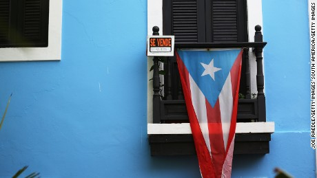SAN JUAN, PUERTO RICO - JULY 01:  A for sale sign is seen hanging from a balcony next to a Puerto Rican flag in Old San Juan as the island's residents deal with the government's $72 billion debt on July 1, 2015 in San Juan, Puerto Rico. Governor of Puerto Rico Alejandro Garc?a Padilla said in a speech recently that the people of Puerto Rico will have to make sacrifices and share the responsibilities to help pull the island out of debt. (Photo by Joe Raedle/Getty Images)