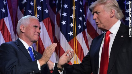 Republican presidential elect Donald Trump (R) reaches to his Vice President elect Mike Pence during election night at the New York Hilton Midtown in New York on November 9, 2016.