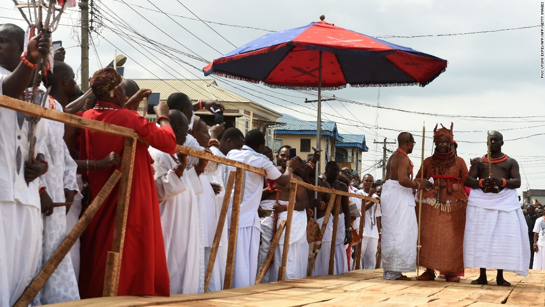 Newly crowned 40th Oba, or king, of the Benin kingdom, Oba Ewuare II , walks on a wooden bridge assisted by palace aides to perform the rite during his coronation.