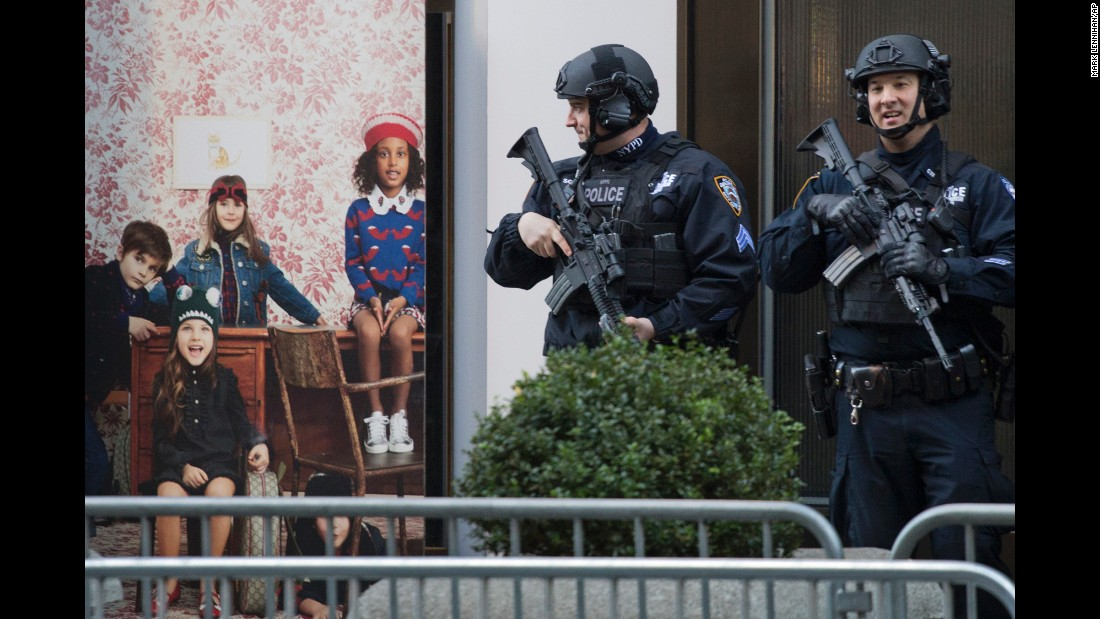 Members of the New York Police Department's counterterrorism squad stand outside Trump Tower -- and next to this Gucci store window -- on Thursday, November 17.