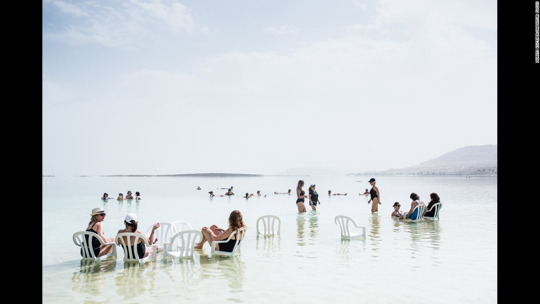Tourists relax on plastic chairs inside the lake.