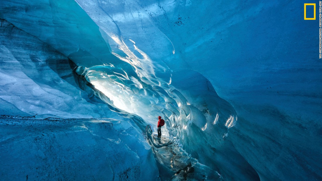 "Photo: Tom Schifanella, USA: ""Since 2000, Icelandic glaciers have lost 12% of their size, in less than 15 years. Pictured here, Icelandic guide Hanna Pétursdóttir admires an ice cave inside the Svínafellsjökull Glacier, which she notes is rapidly expanding due to the effects of global warming,"" wrote Schifanella. <em>Via National Geographic Your Shot</em>"